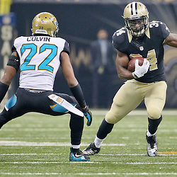 Dec 27, 2015; New Orleans, LA, USA; New Orleans Saints running back Tim Hightower (34) runs Jacksonville Jaguars cornerback Aaron Colvin (22) during the first quarter of a game at the Mercedes-Benz Superdome. Mandatory Credit: Derick E. Hingle-USA TODAY Sports