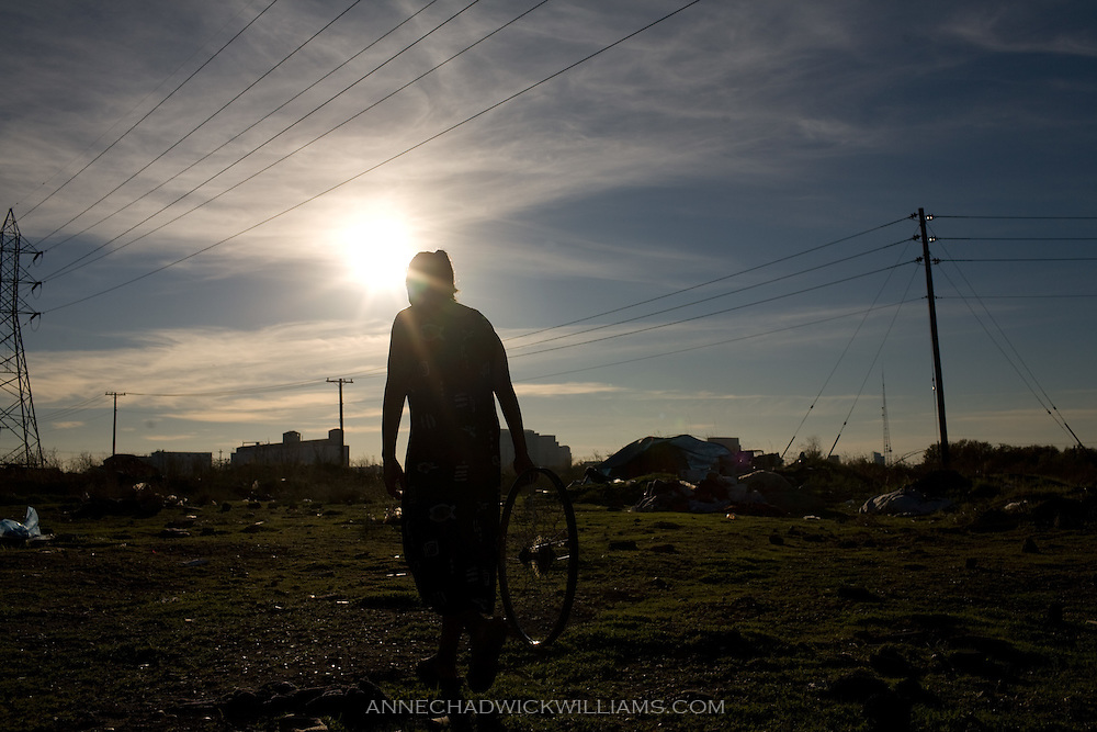 Homeless woman Eve carries on old bike wheel at her camp in Sacramento, CA on November 17, 2008.