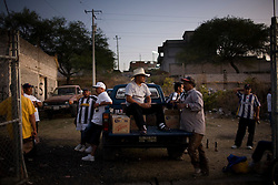 Men drink beer in the late afternoon in Tejaro, Michoacan, a city known for sending scores of illegal immigrants to the US.  Most of these men have spent time working the the United States and used their earnings to build their homes and support their families here in Mexico.  They love their country but say there are no work options in their small town.