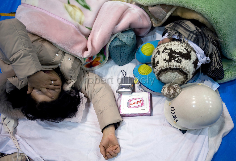 A woman weeps as she listens to the latest news on a transistor radio about the nuclear power plant explosion in Iwaki City, northeastern Japan on 12 March, 2011. Around 300 people, many affected by the explosion, others by the magnitude 8.8 temblor that struck northeast  Japan on 11 March, took shelter at the ad hoc shelter set up inside a local gymnasium about 30 km from the nuclear accident.  Photographer: Robert Gilhooly