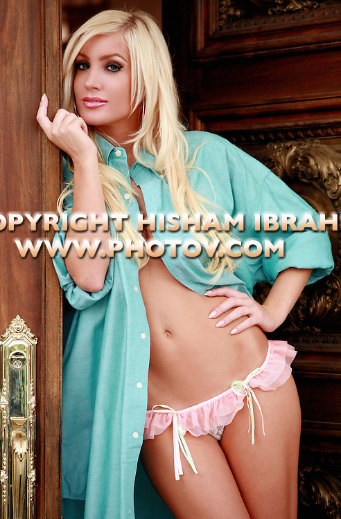 "Young blonde woman wearing bikini and fully unbuttoned shirt standing in doorway. ""Welcome Home""."