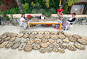 Lea Delos Reyas (1L)  and other locals sell local crafts such as weaved baskets made by the Iriya tribe, Mindoro's indigenous people, in Puerto Galera, the Philippines.