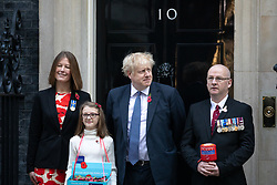 © Licensed to London News Pictures. 28/10/2019. London, UK. British Prime Minister Boris Johnson (3R) buys a poppy from fundraisers for the Royal British Legion on the doorstep of 10 Downing Street. Photo credit : Tom Nicholson/LNP
