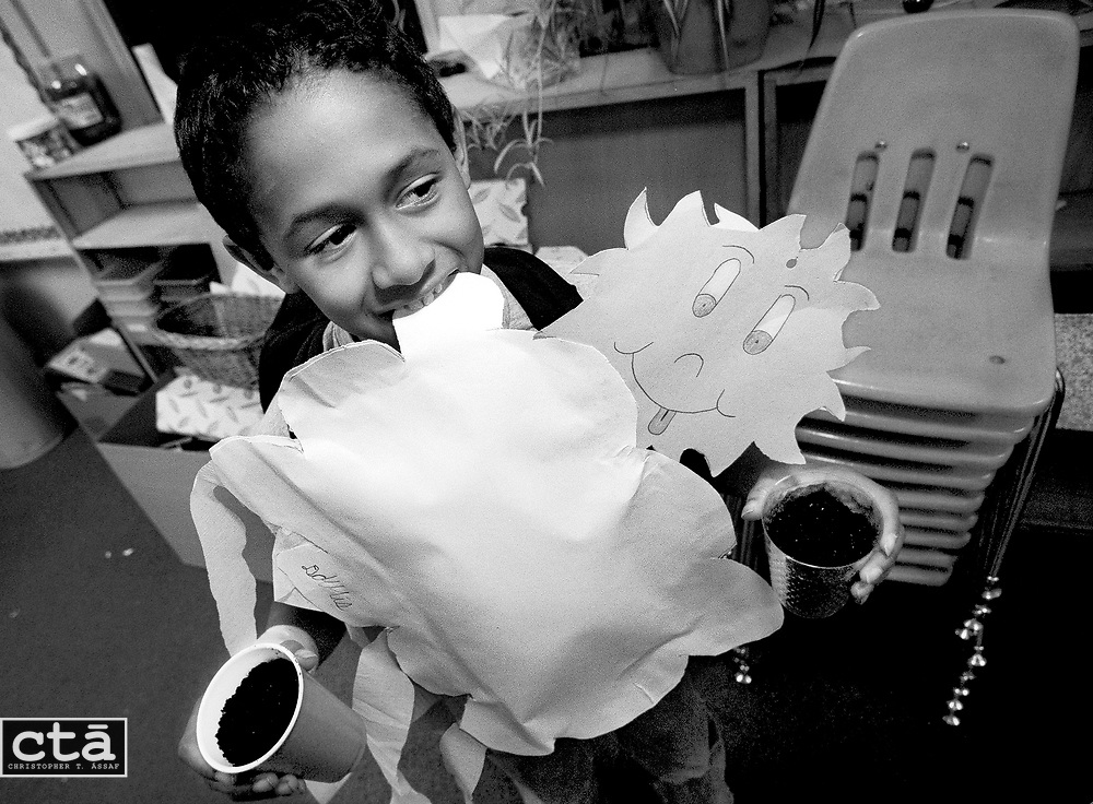Hands and mouth full with an art project and science experiments, second-grader Darris Vann waits to say good-bye to his teacher before leaving the school.