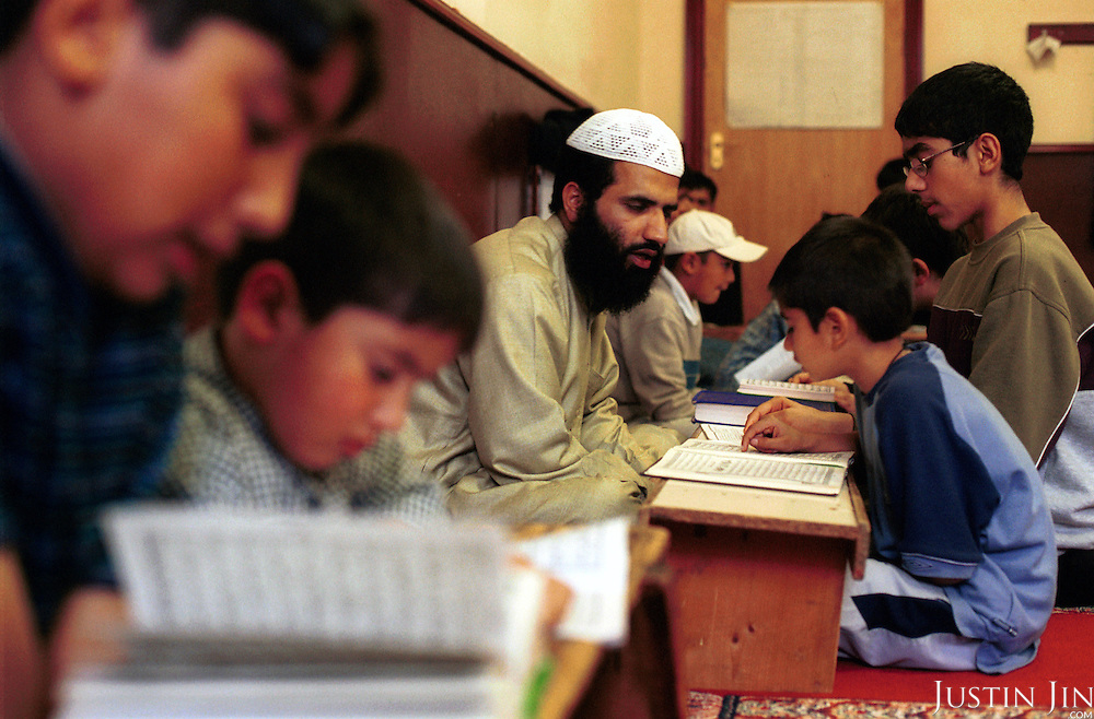 In one of the highly-publicised cases since the September 11 attack on America, Imam Shafiq ur Rehman is pending deportation to Pakistan for allegedly sponsoring terrorism in Kashmir... Rehman, a soft-spoken Pakistani, has been leading prayers and teaching the Koran to kids since his arrival in Britain seven years ago. The British government now accused him of fundraising and recruiting in Britain for a Kashmiri independence group in Pakistan. Rehman admitted only sending money for building hospitals and schools and putting British Muslims in touch with the group. ..Oldham is scene of heavy rioting by Asian youths in the summer of 2001...Photo by Justin Jin. Oldham, Northern England, November 2001.