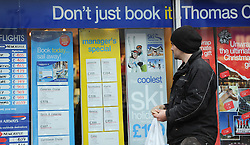 FILE PICTURE © Licensed to London News Pictures. 22/11/2011..Redcar, Cleveland..A man looks at holiday offers in the window of Thomas Cook in Redcar in Cleveland...Photo credit : Ian Forsyth/LNP