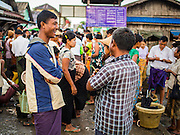 08 NOVEMBER 2014 - SITTWE, RAKHINE, MYANMAR:  Men wait to bid on fresh fish brought into the pier in Sittwe. Fish are auctioned off as they are brought onto the pier. Sittwe is a small town in the Myanmar state of Rakhine, on the Bay of Bengal.  PHOTO BY JACK KURTZ