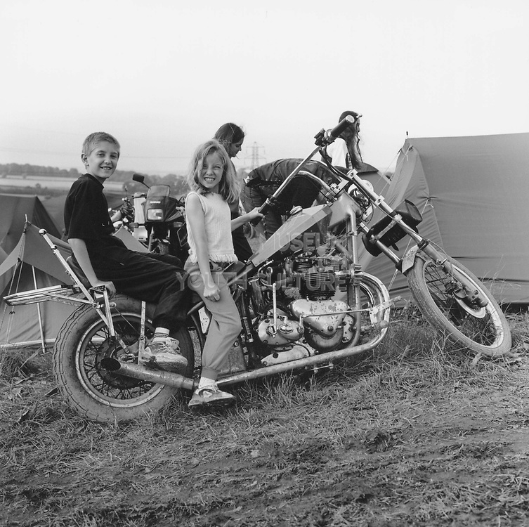 Two kids sitting on a motorbike at a Rock and Blues festival