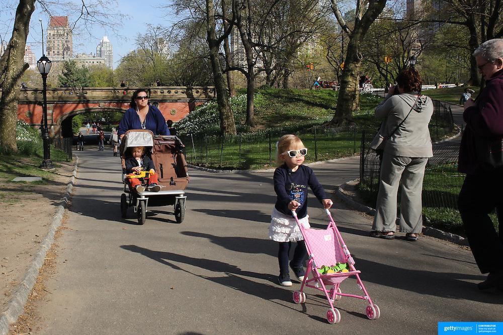 People walk during a warm spring day in Central Park, Manhattan, New York, USA. Photo Tim Clayton