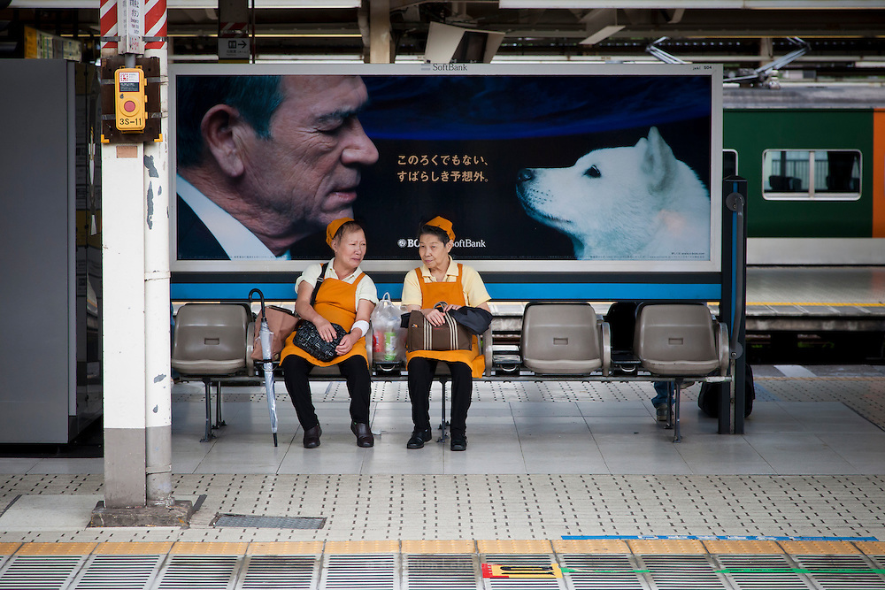 TOKYO, JAPAN, 30 SEPTEMBER - Shinagawa station. Two women wearing orange uniform are seating in front of a commercial with Tommy Lee Jones and a white dog -  September 2012