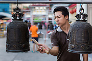 09 FEBRUARY 2014 - HAT YAI, SONGKHLA, THAILAND: A man rings a prayer bell during Lunar New Year in the Tong Sia Siang Tueng temple in Hat Yai. Hat Yai was originally settled by Chinese immigrants and still has a large ethnic Chinese population. Chinese holidays, especially Lunar New Year (Tet) and the Vegetarian Festival are important citywide holidays.     PHOTO BY JACK KURTZ