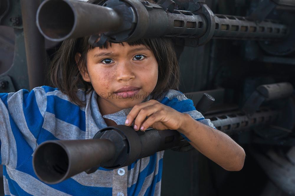 Kid on military gun<br /> Mabaruma<br /> GUYANA<br /> South America