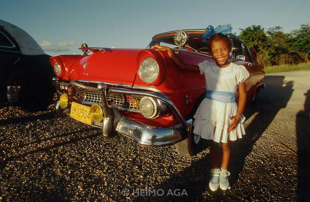 CUBA, SANTIAGO DE CUBA..Posing with daddy's re-revolutionary 1956 vintage Ford convertible..(Photo by Heimo Aga)