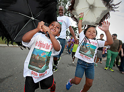 29 August 2014. Lower 9th Ward, New Orleans, Louisiana. <br /> Survivors of the storm. Participants of a  touching second line parade along Tennessee Street in the Lower 9th Ward in memory of those who perished in the storm 9 years ago. <br /> Photo; Charlie Varley/varleypix.com