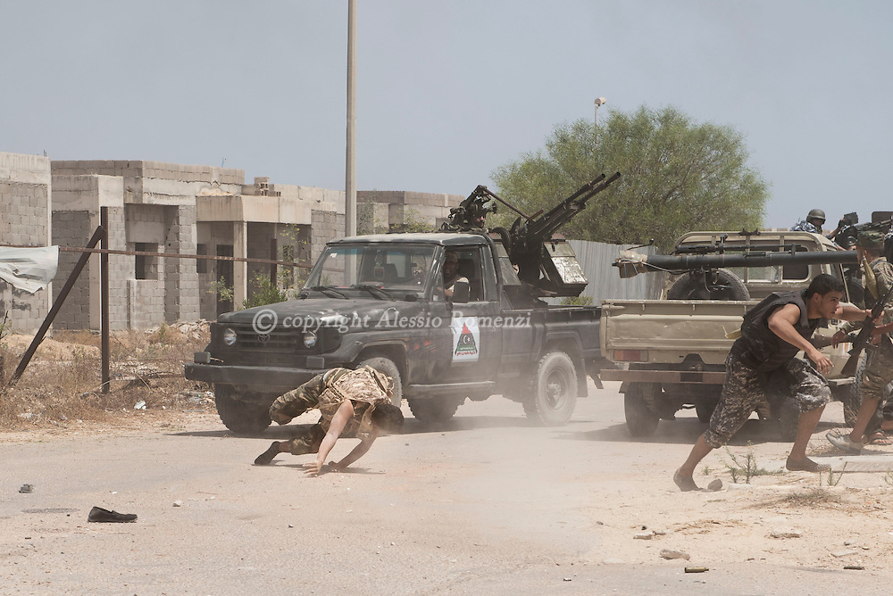 Libya: a fighter affiliated with Libya's Government of National Accord's (GNA) rolls on the ground right after being shot on his leg during clashes with ISIS in 700 neighbourhood in Sirte. Alessio Romenzi