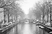 Snow falls over the canal along Spiegelgracht in Amsterdam, with the spires of the Rijksmuseum scene through the clouds. March 2013.