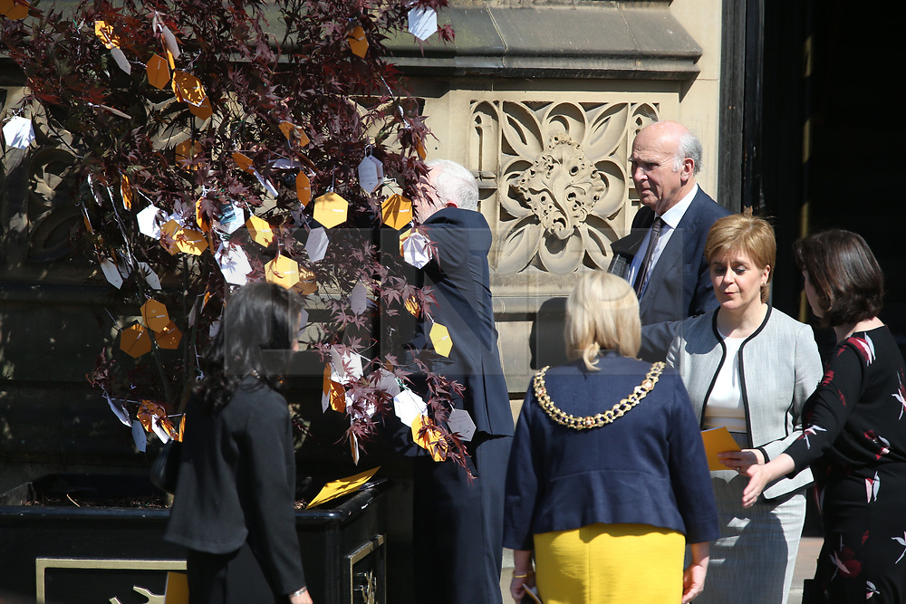 © Licensed to London News Pictures. 22/05/2018. Manchester, UK. Picture shows Jeremy Corbyn placing a message deep in the branches of a tree at the memorial service at Manchester cathedral. Today marks the first anniversary of the Manchester Arena bombing. 22 people died when Salman Abedi detonated a bomb at an Ariana Grande concert. Photo credit: Andrew McCaren/LNP