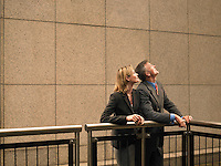 Two people leaning against railing looking up