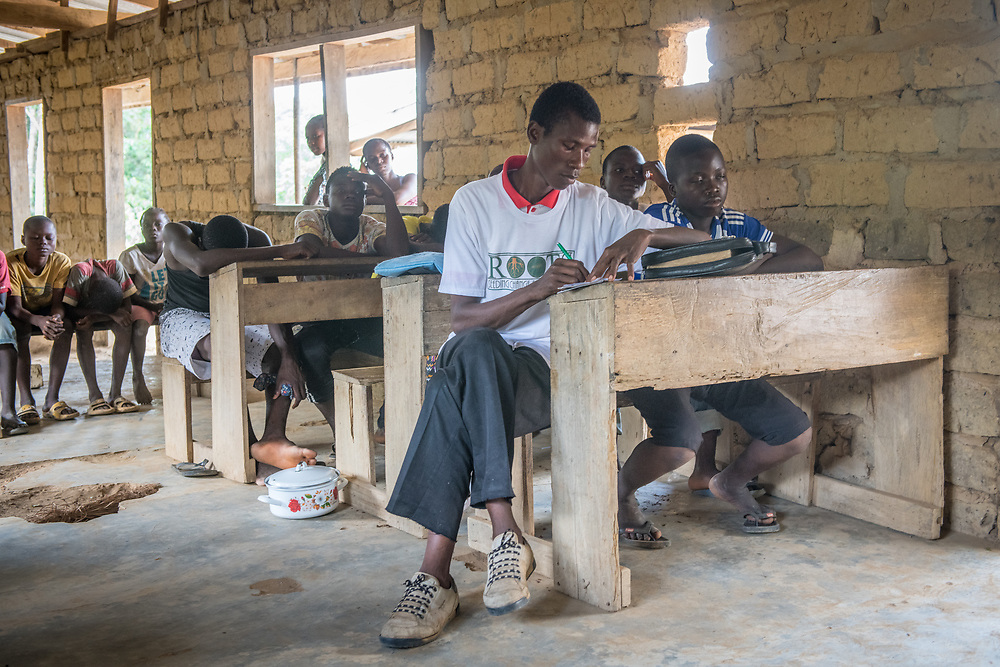 A man focuses on the speaker of a lesson and takes notes  in Ganta, Liberia