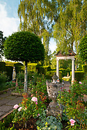 The Triumphal Arch, a stone urn and topiary in the Rose Garden at the Laskett Gardens, Much Birch, Herefordshire, UK
