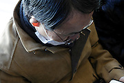 male person sleeping with book in his hand during commute Tokyo Japan