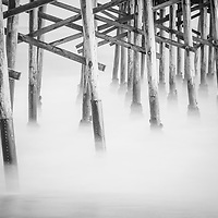 Beach pier poles black and white photo. Pier support poles underneath a California pier along the Pacific Ocean. Copyright ⓒ 2017 Paul Velgos with All Rights Reserved.
