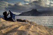 A young lady unfurls a scarf on the rocks at the north end of Ipanema, Rio de Janeiro, Brazil. Photo by Andrew Tobin/Tobinators Ltd