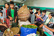 15 JUNE 2013 - YANGON, MYANMAR:  Market vendors ride the Yangon Circular Train to a market outside of Yangon. The Yangon Circular Railway is the local commuter rail network that serves the Yangon metropolitan area. Operated by Myanmar Railways, the 45.9-kilometre (28.5mi) 39-station loop system connects satellite towns and suburban areas to the city. The railway has about 200 coaches, runs 20 times and sells 100,000 to 150,000 tickets daily. The loop, which takes about three hours to complete, is a popular for tourists to see a cross section of life in Yangon. The trains from 3:45 am to 10:15 pm daily. The cost of a ticket for a distance of 15 miles is ten kyats (~nine US cents), and that for over 15 miles is twenty kyats (~18 US cents). Foreigners pay 1 USD (Kyat not accepted), regardless of the length of the journey.     PHOTO BY JACK KURTZ