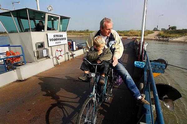 """Nederland, Dieren, 6-10-2005..Het veerpontje """"steeds voorwaarts"""" tussen Dieren en Olburgen. De veerpont heeft het steeds moeilijker omdat vervanging van de oude vaartuigen te duur is. Pont, pontveer, rivier oversteken zonder brug. Veerman, verdwijnend beroep, infrastruktuur, infrastructuur, vaarwegen. Overheidssteun, openbaar vervoer. man met kind op fiets...Foto: Flip Franssen/Hollandse Hoogte"""