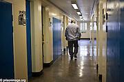 AN elderly prsioner walking dow the wing corridor. HMP & YOI Littlehey. Littlehey is a purpose build category C prison.