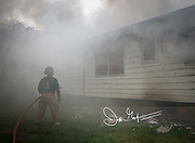 A firefighter holds a firehose outside of a smoking and burning house.