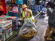 12 JANUARY 2017 - BANGKOK, THAILAND: A traditional food vendor walks through Bo Bae Market. Bo Bae Market is a sprawling wholesale clothing market in Bangkok. There are reportedly more than 1,200 stalls selling clothes made in Thailand and neighboring countries. Bangkok officials have threatened to shut down parts of Bo Bae market, but so far it has escaped the fate of the other street markets that have been shut down.          PHOTO BY JACK KURTZ