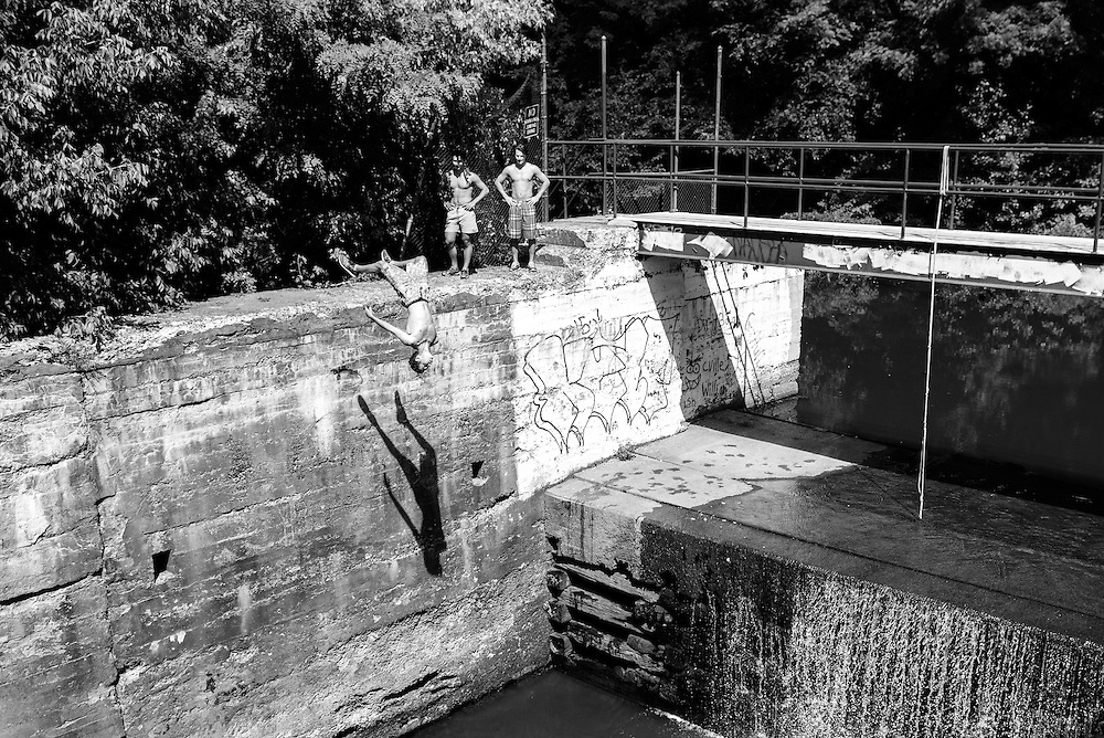High school boys, on break from school, dive off of Lock 60 in Phoenixville, Pa. to cool off on a hot, midsummer day.