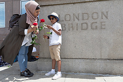 "© Licensed to London News Pictures. 11/06/2017. LONDON, UK.  A woman and a boy (permission for photograph given) with red roses on London Bridge this afternoon. 1,000 red roses with messages of ""love and solidarity"" were given to passers by on London Bridge today.  Photo credit: Vickie Flores/LNP"