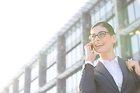 Low angle view of happy businesswoman using cell phone outside office building