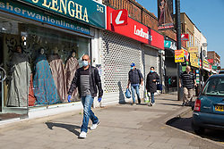 © Licensed to London News Pictures. 22/04/2020. London, UK. People wearing a face masks  walks past closed shops and businesses in Ealing Road, Alperton. The start of the Muslim observation of Ramadan will begin during the Coronavirus lockdown.  Photo credit: Ray Tang/LNP