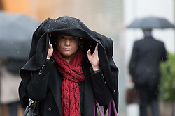 © Licensed to London News Pictures. 28/03/2018. London, UK. A woman covers her head with a coat as she walks from Waterloo Station during rain and wet weather this morning. Photo credit: Vickie Flores/LNP