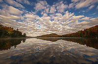 Beautful clouds and a mirror reflection during autumn on Kettle Pond, Groton State Forest, Vermont