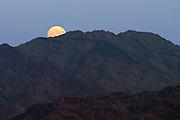 Israel, Judea desert Dead Sea, moon rising over mountains