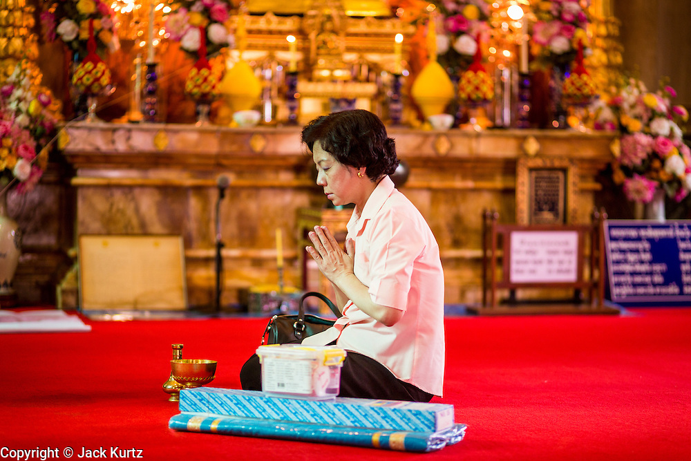 15 JULY 2014 - BANGKOK, THAILAND:   A woman prays in the ubosot (ordination hall) at Wat Rachathiwat Ratchaworawihan on Samsen Soi 9. The temple has a large teak instruction hall, considered one of the finest teak buildings in Asia.   PHOTO BY JACK KURTZ