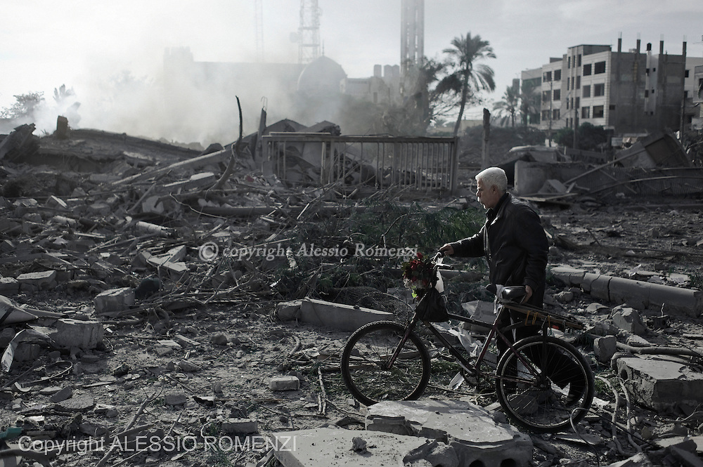 Gaza City: A Palestinian man pass with his bicycle on rubbles of a Hamas Government building destroyed by Israeli airstrike. November 21, 2012. ALESSIO ROMENZI