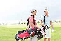 Male golfers communicating at golf course against clear sky