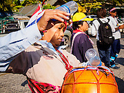 22 DECEMBER 2013 - BANGKOK, THAILAND:  An anti-government protestor plays the drums at a roadblock blocking the road to the home of Yingluck Shinawatra. Hundreds of thousands of Thais gathered in Bangkok Sunday in a series of protests against the caretaker government of Yingluck Shinawatra. The protests are a continuation of protests that started in early November and have caused the dissolution of the Pheu Thai led government of Yingluck Shinawatra. Protestors congregated at home of Yingluck and launched a series of motorcades that effectively gridlocked the city. Yingluck was not home when protestors picketed her home.    PHOTO BY JACK KURTZ