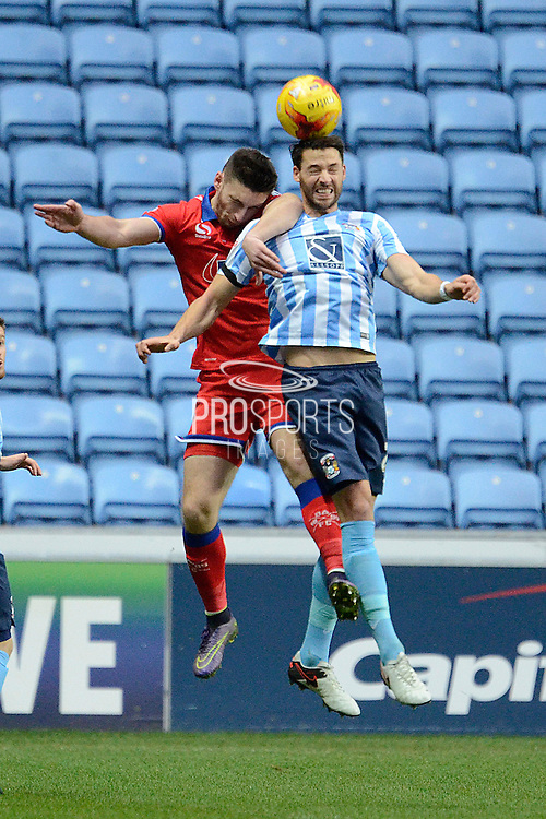 Coventry City defender Aaron Martin and Oldham Athletic striker Jake Cassidy challenge for a header during the Sky Bet League 1 match between Coventry City and Oldham Athletic at the Ricoh Arena, Coventry, England on 19 December 2015. Photo by Alan Franklin.