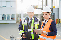 Male and female workers discussing over clipboard in shipping yard