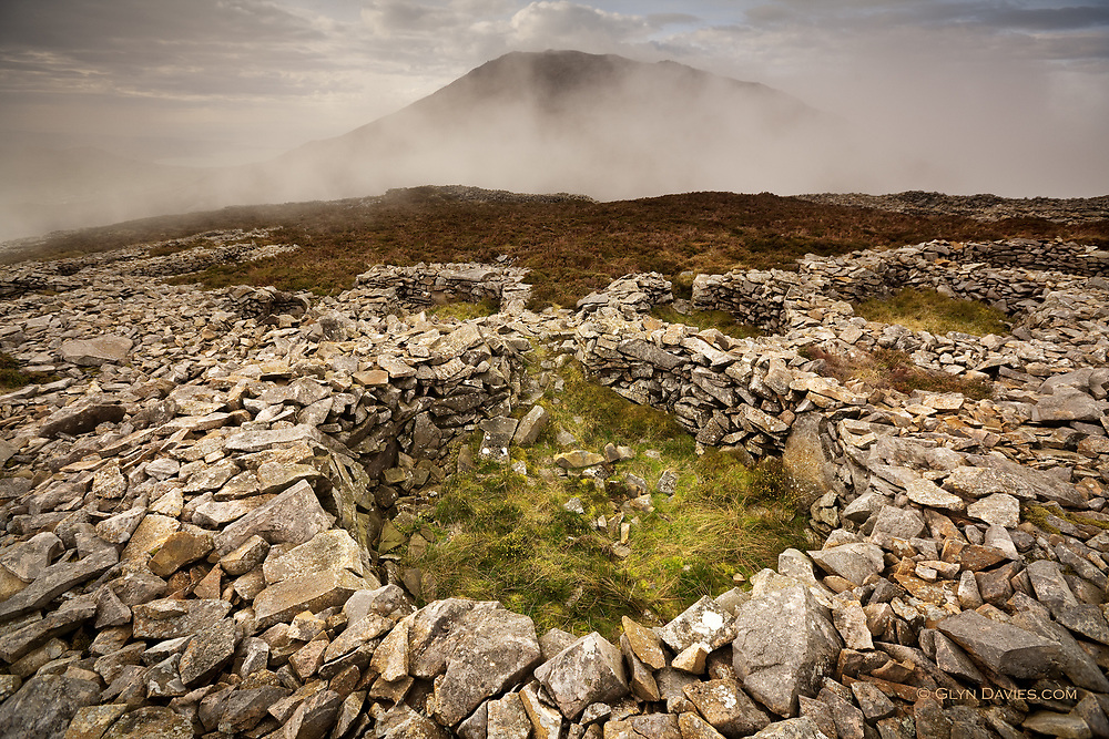 The largest iron age settlement / fortress in Britain, Tre'r Ceiri covers the top of a high Welsh mountain, so high that clouds often pass lower than the summit as here. The highest peak on this peninsula hides behind the mist in the background.