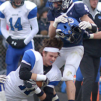 Geneva's Mike Landi has his helmet ripped off by Cary-Grove's Larkin Hanselmann during a tackle in the third quarter of the Class 7A semifinal playoff game in Cary.