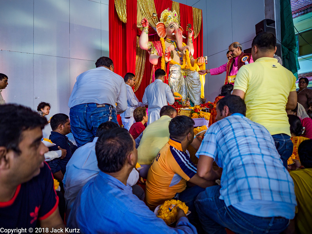 """23 SEPTEMBER 2018 - BANGKOK, THAILAND: Men approach the Ganesha deity to move it to a truck at the Ganesha Festival at Wat Dan in Bangkok. Ganesha Chaturthi also known as Vinayaka Chaturthi, is the Hindu festival celebrated on the day of the re-birth of Lord Ganesha, the son of Shiva and Parvati. The festival, also known as Ganeshotsav (""""festival of Ganesha"""") is observed in the Hindu calendar month of Bhaadrapada, starting on the the fourth day of the waxing moon. The festival lasts for 10 days, ending on the fourteenth day of the waxing moon. Outside India, it is celebrated widely in Nepal and by Hindus in the United States, Canada, Mauritius, Singapore, Thailand, Cambodia, and Burma.    PHOTO BY JACK KURTZ"""
