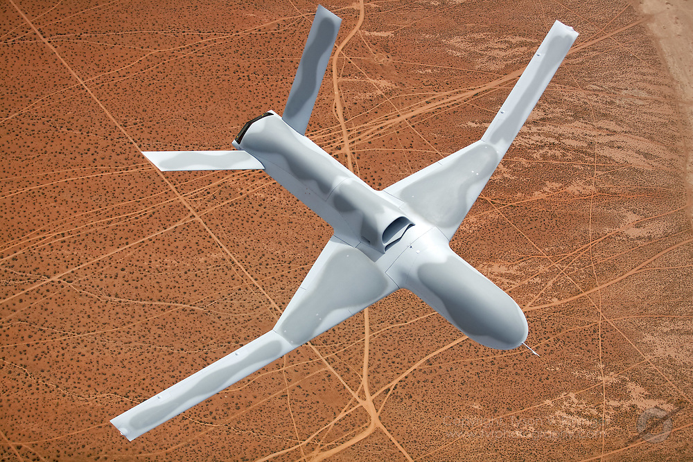 """An aerial view of General Atomics P46 Predator 'C', """"Avenger"""" over the high deserts of Southern California. The latest generation Predator is a jet-powered remotely-piloted vehicle (RPV) that is nearly twice the size of its predecessor. Featuring an internal weapons bay, retractable gear, a blended wing design, top-mounted intake and shielded exhaust, the stealthy airframe can cruise at 50,000 feet and can perform multiple tasks from reconnaisance to attack roles."""