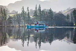 © Licensed to London News Pictures. 21/02/2018. Glenridding UK. The Ullswater Steamer makes it's way from Glenridding to Pooley Bridge along the calm water of Ullswater lake this morning on a sunny day in Cumbria. Photo credit: Andrew McCaren/LNP